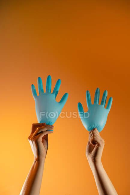 Gesichtslose Person mit Luftballons aus medizinischen Handschuhen, die winkende Handgeste auf orangefarbenem Hintergrund zeigen — Stockfoto