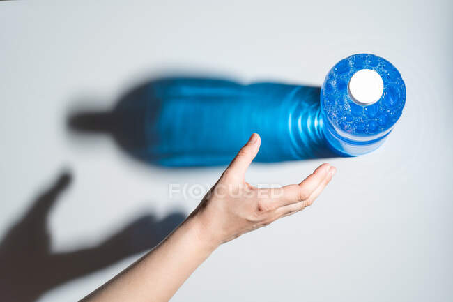 Crop faceless person reaching out hand for plastic and transparent bottle of blue liquid with bubbles located on white surface — Stock Photo