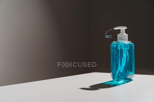 Botella transparente de plástico con jabón líquido azul situado en la superficie blanca y chorro de jabón delgado que sale del dispensador blanco - foto de stock