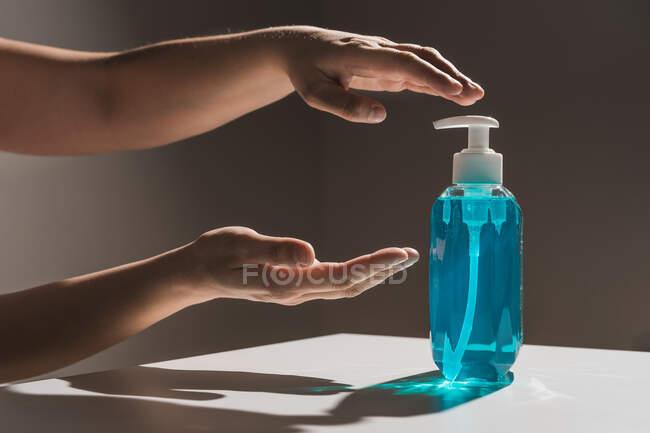 Cortar pessoa sem rosto puxando as mãos para plástico garrafa de sabão líquido azul com distribuidor branco no interior localizado na mesa branca com sombra — Fotografia de Stock