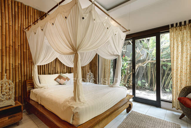 Bright interior of bedroom in hotel with bamboo wall and cozy canopy bed in Bali — Stock Photo