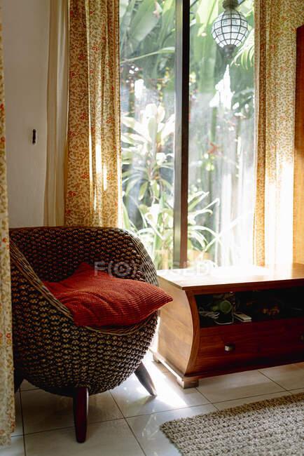 Интерьер спальни с удобным плетеным креслом с подушками — стоковое фото