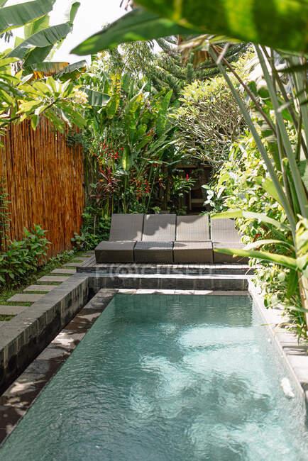 Pátio acolhedor com piscina rodeada por plantas tropicais e cerca de bambu em Bali — Fotografia de Stock