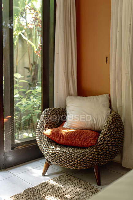 Interior of bedroom with comfortable wicker armchair with cushions — Stock Photo