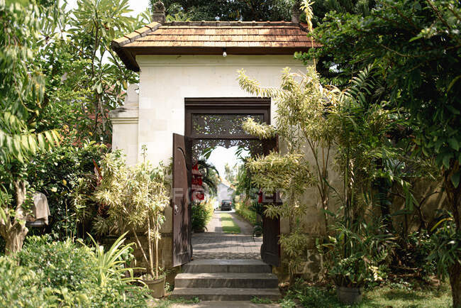 Stone walkway leading to entrance of cottage surrounded by exotic plants on sunny day in Bali — Stock Photo