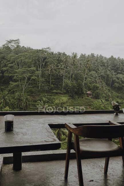 De cima do terraço com cadeiras de madeira e mesas perto de bungalow com telhado de palha cercado por plantas tropicais no dia sombrio em Bali — Fotografia de Stock