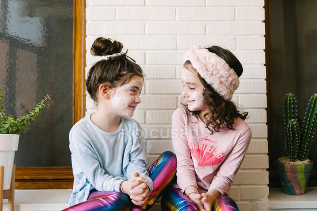 Gioioso ridere ragazze in vestiti simili e maschera applicata seduto sul tavolo di legno a casa divertendosi contro muro bianco mattone — Foto stock