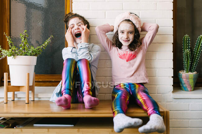 Joyful laughing girls in similar clothes and applied face mask sitting on wooden table at home having fun against brick white wall — Stock Photo