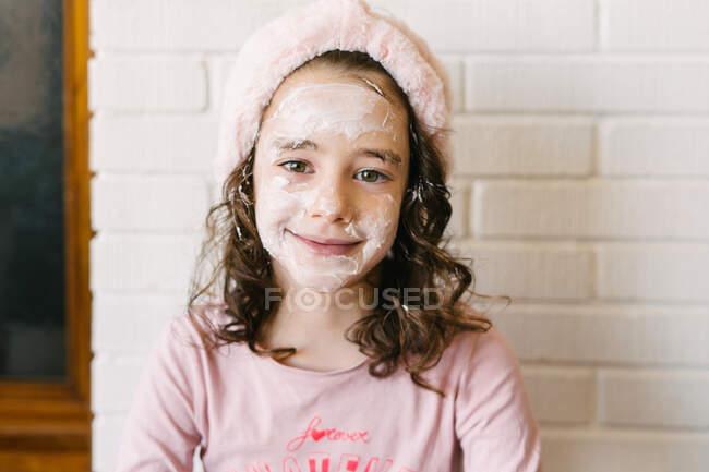 Joyeux petit garçon souriant aux cheveux bouclés en pyjama rose et bandeau assis près du mur de briques blanches dans un masque facial et regardant la caméra — Photo de stock