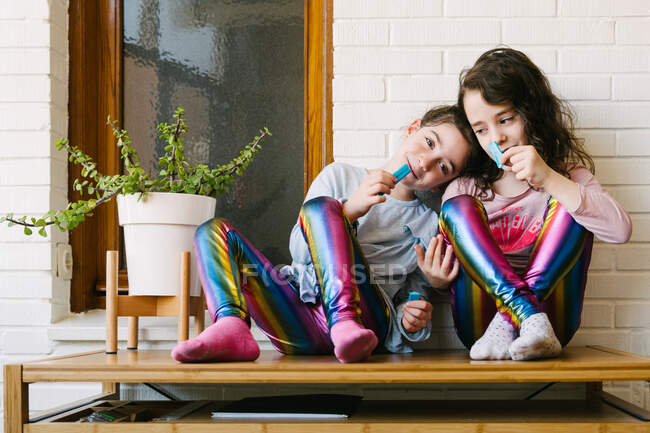 Smiling little sisters sitting on table and eating yummy blue chewing candy having fun and looking at each other while resting at home during weekend — Stock Photo