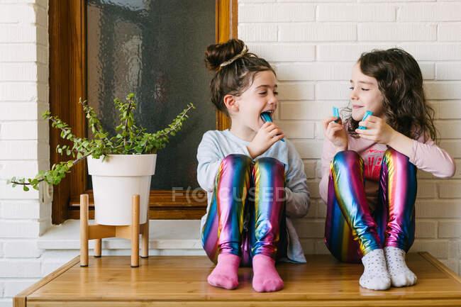 Улыбающиеся сёстры сидят на столе и едят вкусные голубые жевательные конфеты, развлекаясь и глядя друг на друга, отдыхая дома в выходные. — стоковое фото