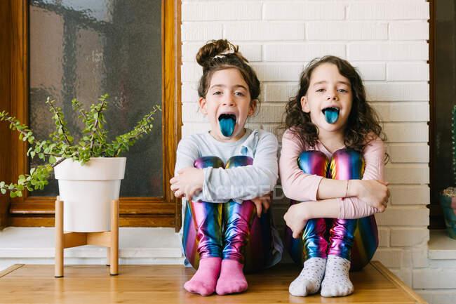 Две улыбающиеся сестры, торчащие голубым языком после того, как съели жвачку — стоковое фото