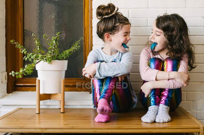 Dos hermanas sonrientes sacando una lengua azul después de comer un chicle azul - foto de stock