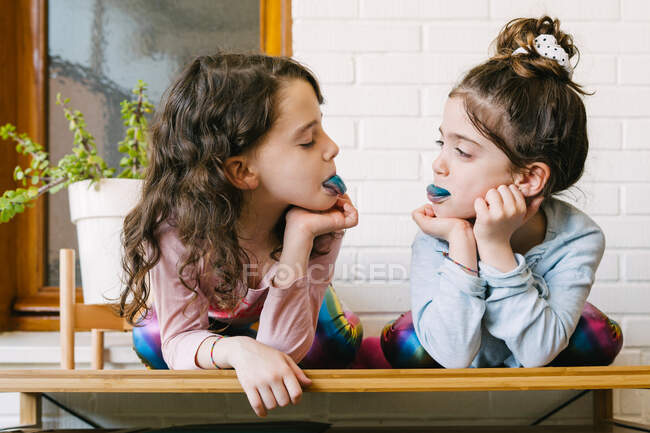 Two smiling sisters sticking out a blue tongue after eating a blue bubble gum — Stock Photo