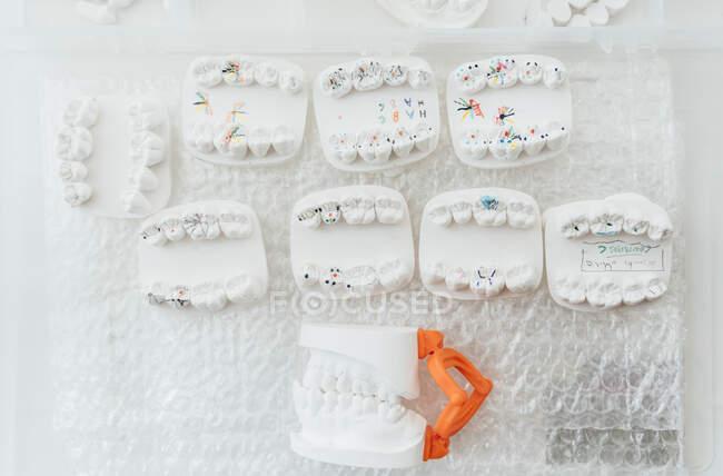 Vista superior de varios conjuntos de coronas dentales y modelo de mandíbula para estudiar odontología dispuesta en recipiente de plástico - foto de stock