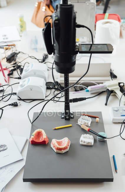 De cima de modelos de maxilar dental e coroas colocadas na mesa com queimador e lápis em laboratório moderno — Fotografia de Stock