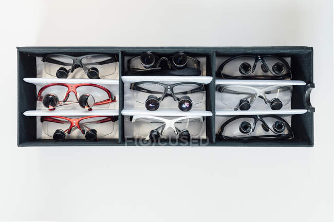 Top view of multicolored dentist medical glasses with binocular lenses arranged in black box placed on white table in laboratory — Stock Photo