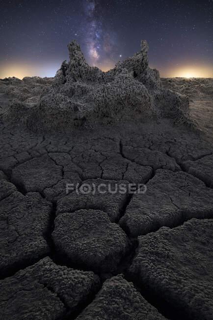 Суха тріснута земля з сонцем і зорями на небі. — стокове фото