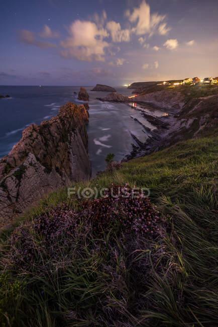 Чудовий краєвид скелястого берега океану з грубими скелями і тихою водою під величним небом під сонцем. — стокове фото