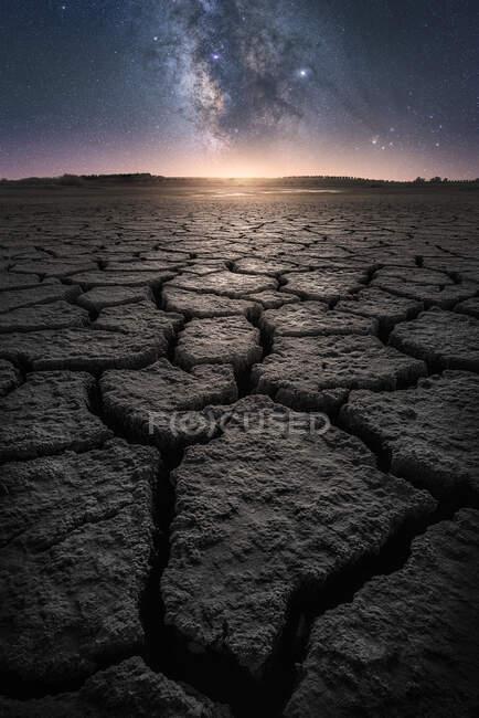 Terre fissurée sèche avec coucher de soleil et étoiles dans le ciel — Photo de stock