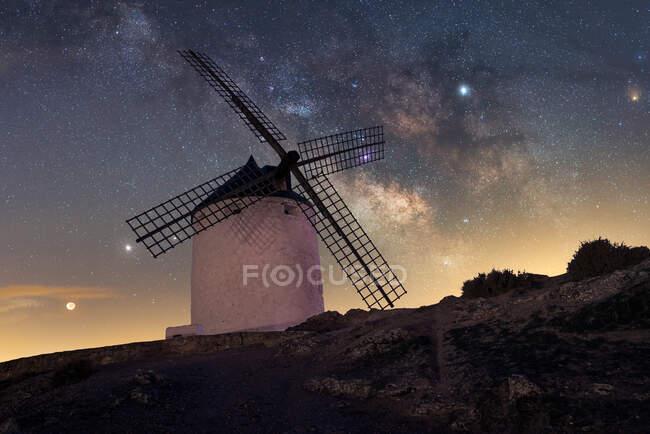 Вітряк на пагорбі з зоряним небом на тлі — стокове фото