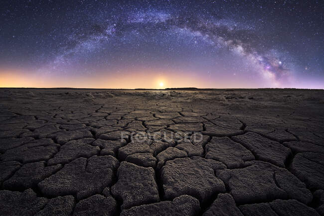 Dry cracked land with setting sun and stars in sky — Stock Photo