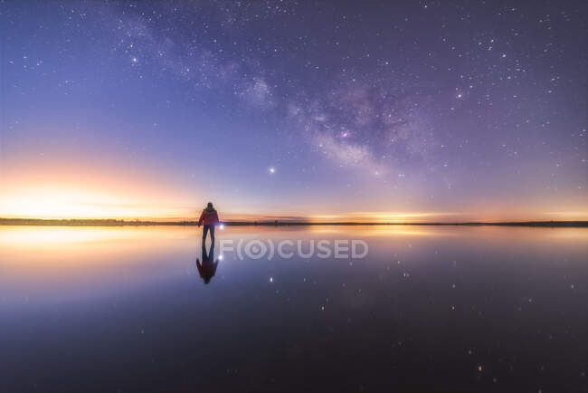 Silhouette of anonymous man standing on reflection surface of water and reaching out to starry colorful night sky with milky way — Stock Photo