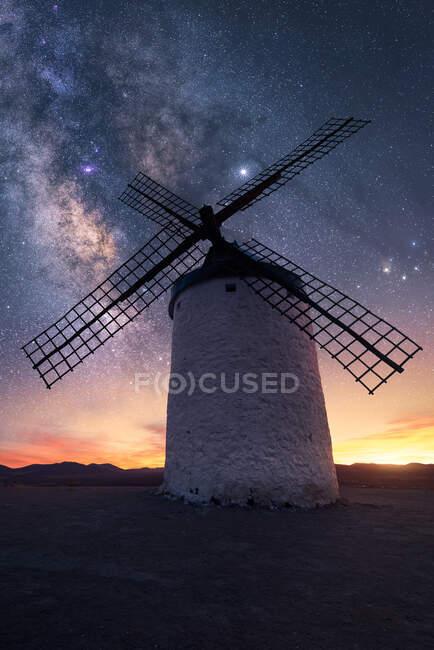 Molino de viento en la colina con cielo estrellado en el fondo - foto de stock