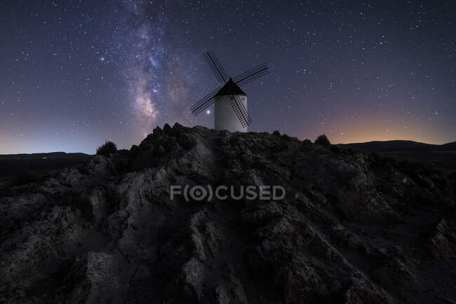 Windmill on hill with starry sky on background — Stock Photo