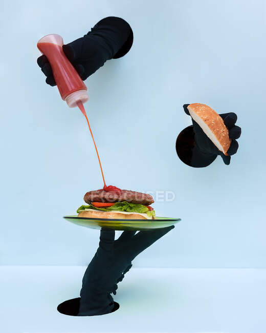 Hand of anonymous people in black gloves holding plate with burger and spilling ketchup on patty against blue background — Stock Photo