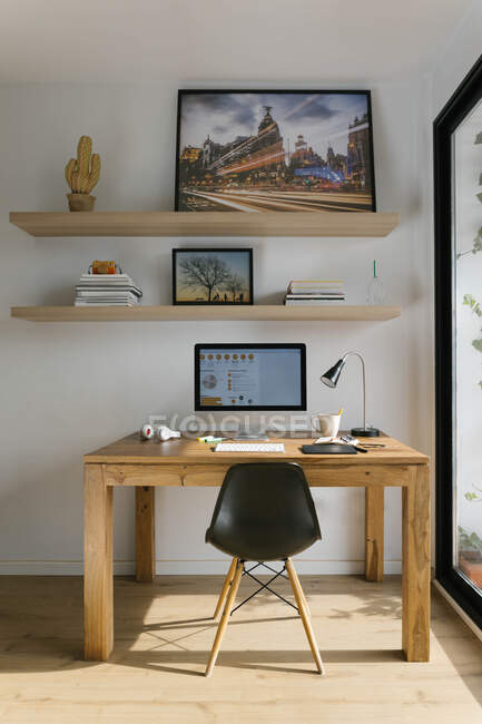 Interior of modern workspace with personal computer tablet and headphones on wooden desktop stylish chair and bookshelves above desk locating near big glass wall in light trendy living room at home — Stock Photo