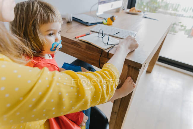 Side view of unrecognizable female entrepreneur in casual clothes sitting at desk and using notepad while working with little daughter in lap at home — Stock Photo