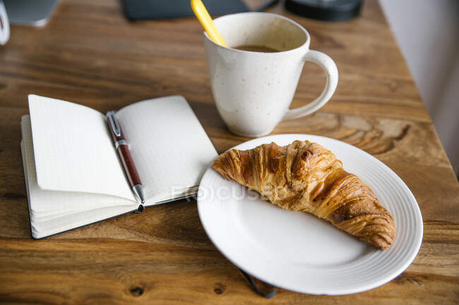 Cup of hot coffee, opened planner and plate with crispy fresh croissant on wooden table — Stock Photo