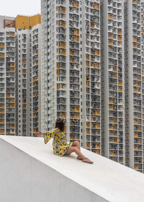 Unrecognizable relaxed female in multicolored dress sitting with arms outstretched on concrete sloping roof and looking at residential skyscrapers in Hong Kong in China — Stock Photo