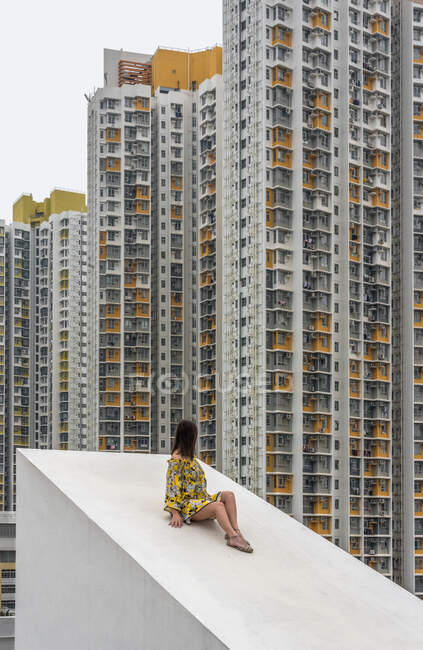 Unrecognizable relaxed female in multicolored dress sitting on concrete sloping roof and looking at residential skyscrapers in Hong Kong in China — Stock Photo