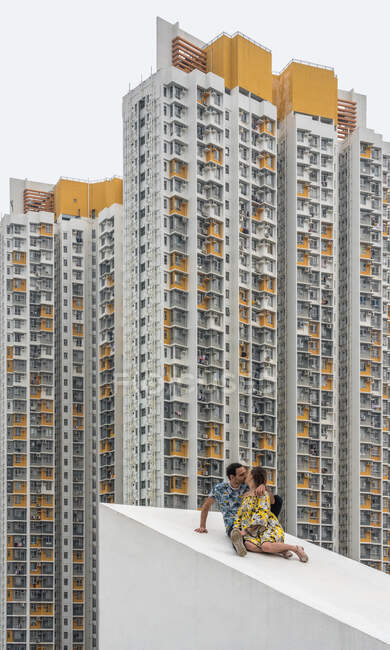 Adult man and faceless girl in colorful dress kissing on concrete sloping roof against facades of spotted residential skyscrapers in Shek Kip Mei — Stock Photo