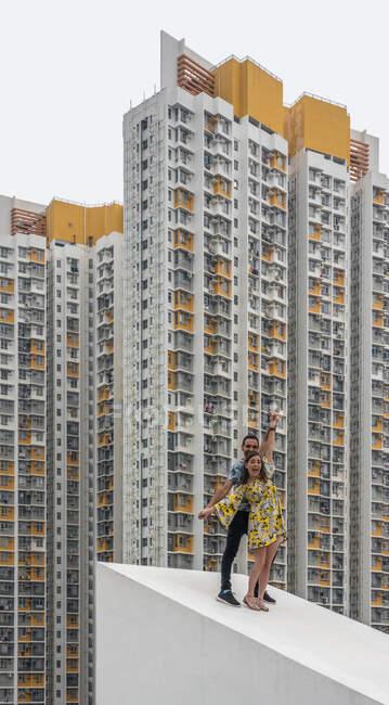 Веселий дорослий чоловік і дівчинка у барвистому одязі веселяться разом на бетонному похилому даху проти фасадів плямистих житлових хмарочосів у Шек Кіп Мей. — стокове фото