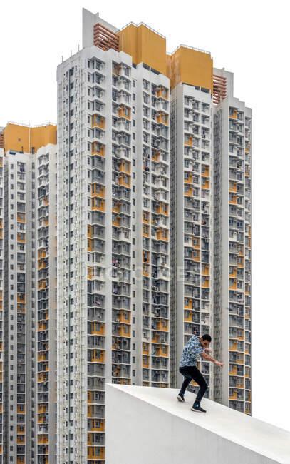 Нерозслаблений чоловік у повсякденному одязі, прикидаючись присідає на бетонний похилий дах до екстер