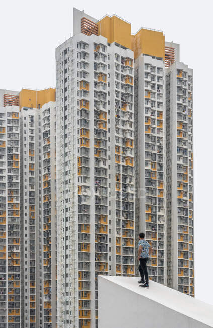 Relaxed male in casual clothes posing on concrete sloping roof looking at exteriors of residential skyscrapers with gray and yellow spots in Hong Kong — Stock Photo