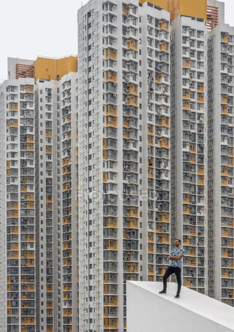 Homem relaxado em roupas casuais posando no telhado inclinado concreto contra exteriores de arranha-céus residenciais com manchas cinza e amarelo em Hong Kong — Fotografia de Stock