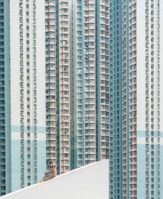 Donna rilassata in abito a righe bianche e scure seduta sul tetto spiovente di cemento e guardando la fotocamera a Hong Kong in Cina — Foto stock