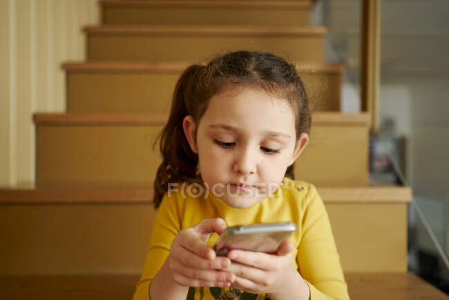 Calm small girl in casual yellow clothes focusing on screen with interest and interacting with smartphone while sitting alone on stairs in corridor of country house — Stock Photo