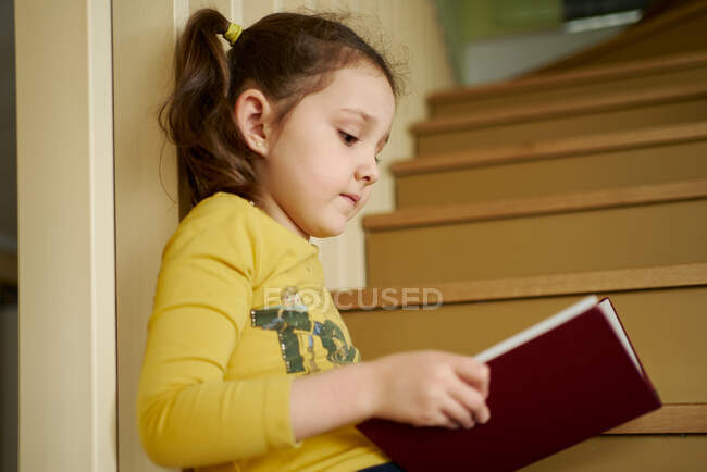 From below focused little schoolgirl with ponytail in casual clothes reading book with interest while sitting alone on stairs in quiet corridor of multistory building — Stock Photo