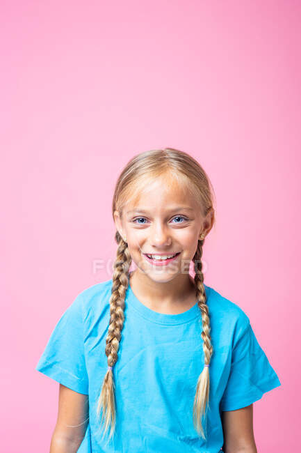 Cute girl with blond braids and in blue t shirt looking at camera against pink background — Stock Photo