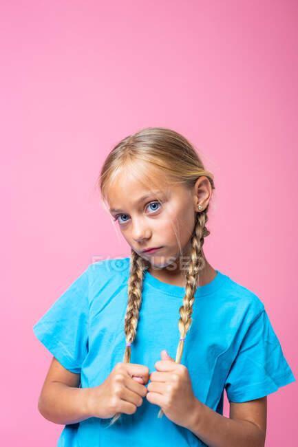 Милая девушка с светлыми косичками и в синей футболке смотрит в камеру на розовом фоне — стоковое фото