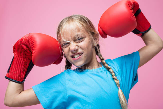 Aggressive little girl in boxing gloves demonstrating biceps and looking at camera while representing power — Stock Photo
