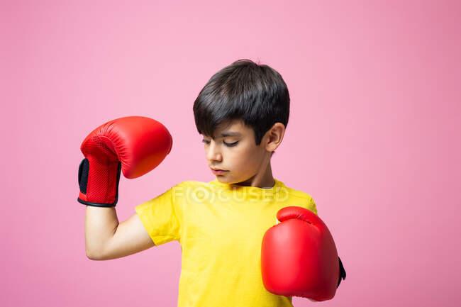 Маленький хлопчик у жовтій футболці і червоні боксерські рукавички, що дивляться на камеру і б'ють повітря під час тренування проти рожевого фону — стокове фото