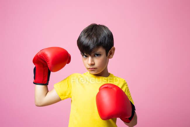 Мальчик в жёлтой футболке и красных боксёрских перчатках смотрит в камеру и бьёт по воздуху, тренируясь на розовом фоне. — стоковое фото
