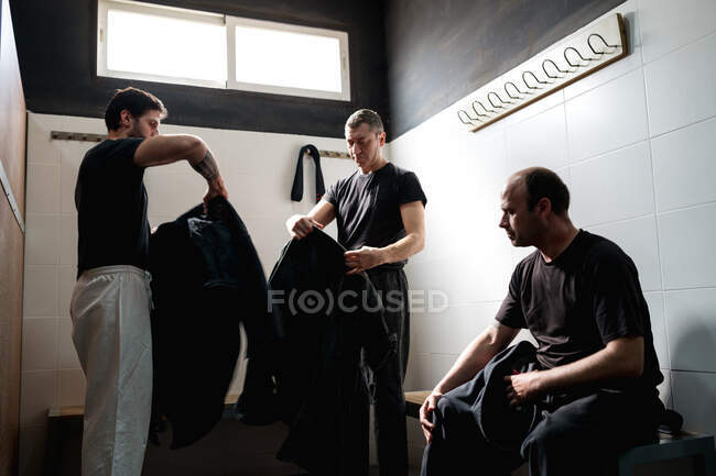 Grupo de lutadores adultos sérios vestindo quimono preto enquanto se prepara para o treinamento de kajukenbo no moderno clube de artes marciais vestiário — Fotografia de Stock