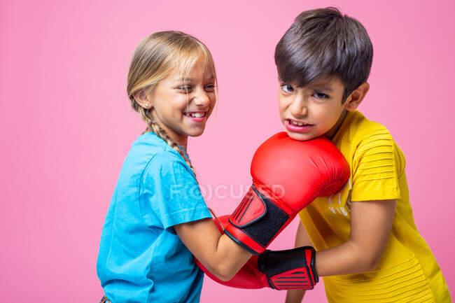 Вид сбоку веселый мальчик и девочка бьют друг друга в челюсть и живот во время тренировки по боксу против — стоковое фото